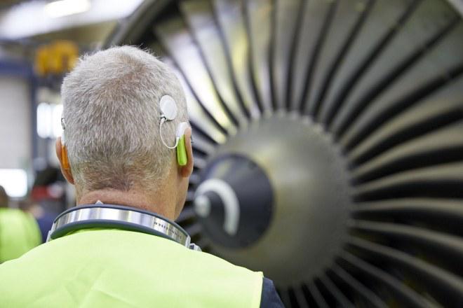 Foto eines Teilnehmers vor einer Antriebsdüse des Flugzeugs, das Implantat ist gut sichtbar